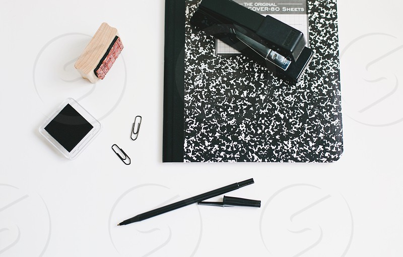 Education school supplies office white background black and white composition book tablet homework learning stapler pen paper clips ink pad rubber stamp white desk desktop back to school  photo