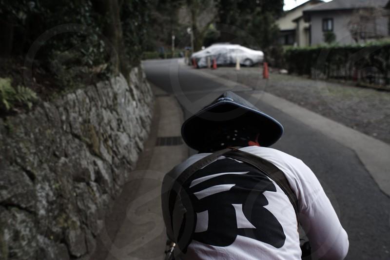 person wearing sakkat riding bike near gray wall during daytime photo