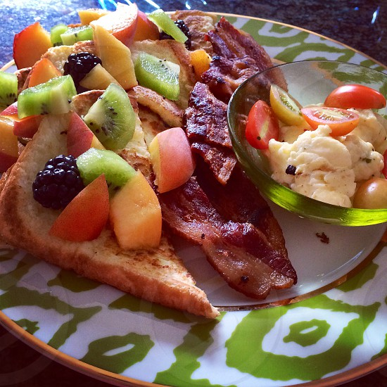 French Toast Topped with Fruit with Crispy Bacon served with Scrambled Eggs and Cherry Tomato for brunch  photo