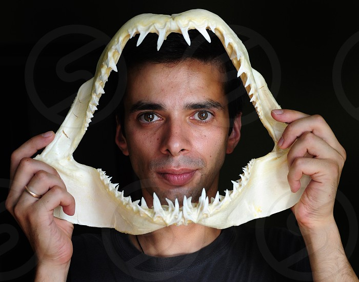man holding beige shark tooth photo