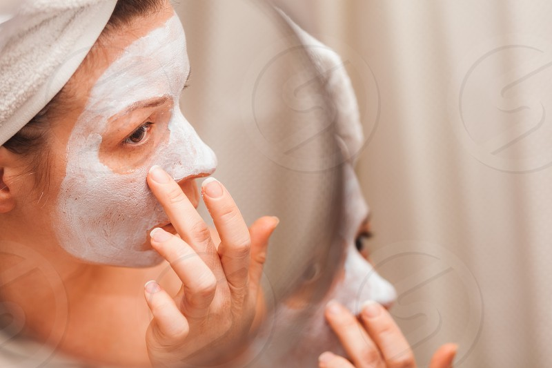 Young woman putting a cream on her face photo