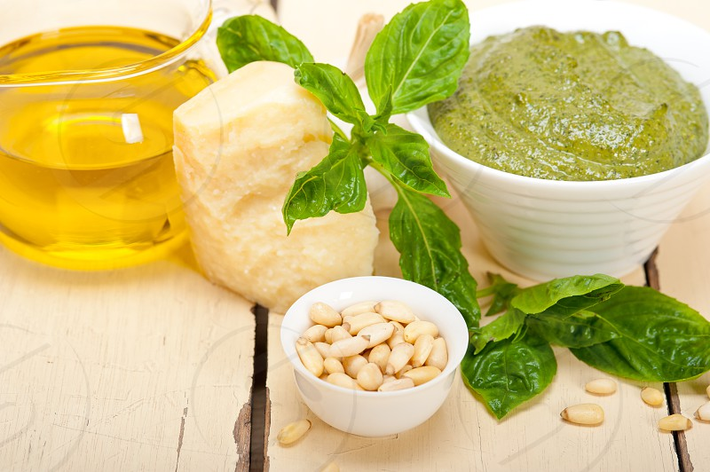Italian traditional basil pesto sauce ingredients on a rustic table photo
