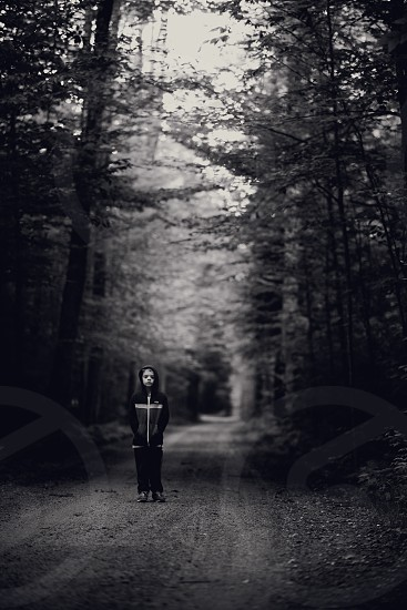 boy standing in forest gray scale photography photo