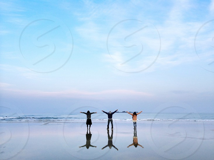 3 people standing on beach near body of water photo