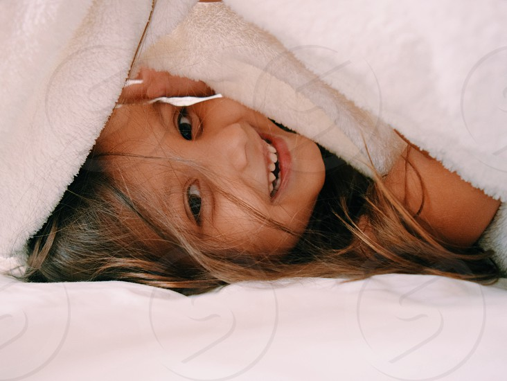 girl covering herself with white blanket photo