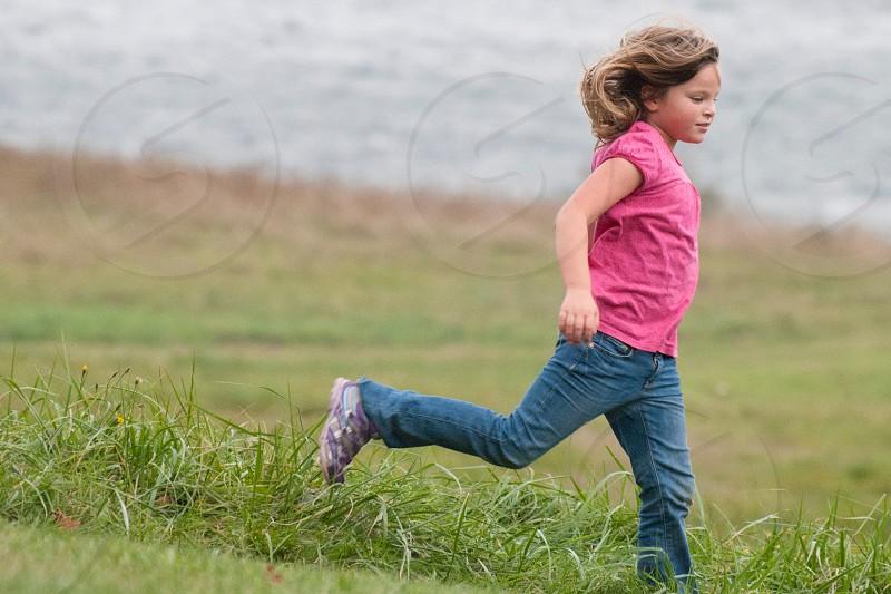 girl running on grass field photo