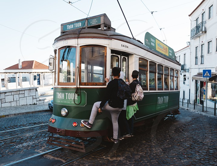 2 man with backpack hitch on green and white tram during daytime photo