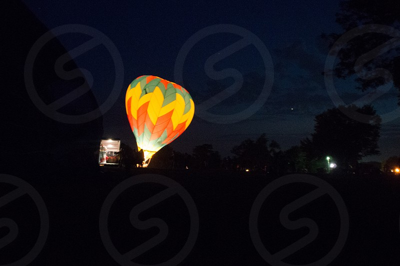 yellow orange green hot air balloon floating through night sky photo