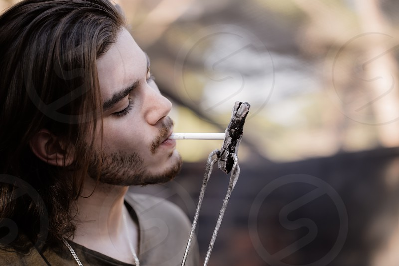 Portrait of a handsome young man with a beard lighting a cigarette from charcoal holding his by barbecue tongs. photo