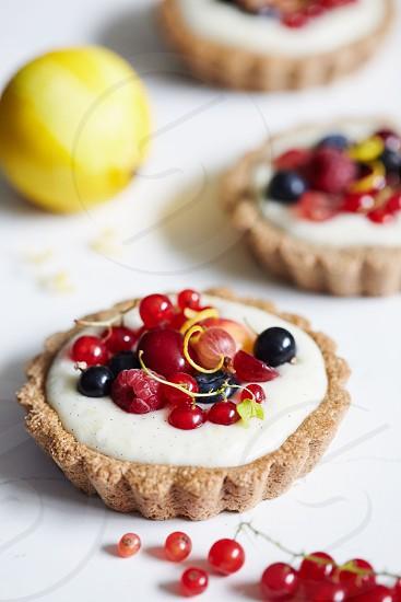 Lemon cream tarts topped with fresh berries and lemon. photo