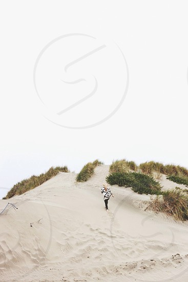 person walking in gray sand photo