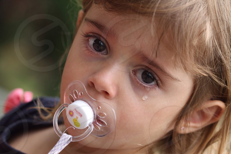 girl crying with a pacifier on her mouth photo