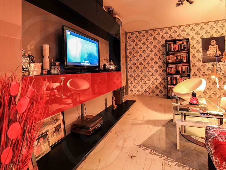 flat screen tv on a wall mounted shelf near a glass table photo