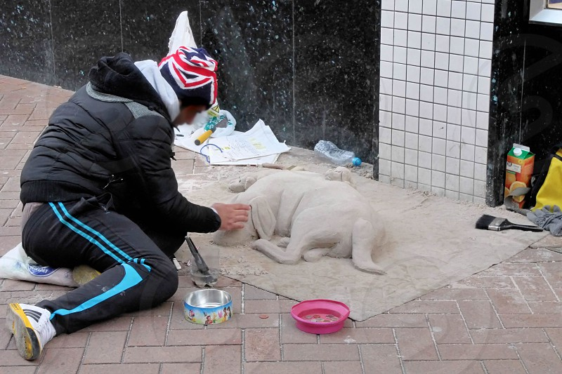 Street performer modelling a dog out of sand photo