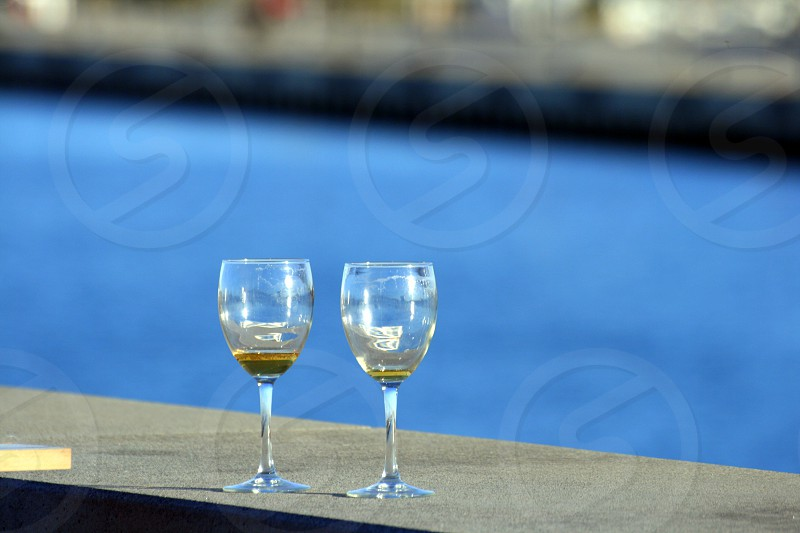 two wine glasses near swimming pool during daytime photo