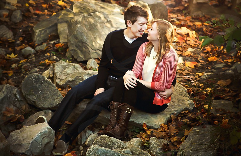man and woman smiling at each other on rocks with autumn leaves photo