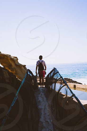 man in backpack on cliff bridge photo
