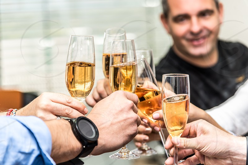 Group of people celebrating in an office with champagne glasses. photo