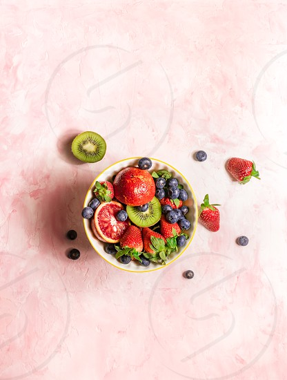 Fruit bowl with fresh kiwi strawberries and blueberries on a pink background photo
