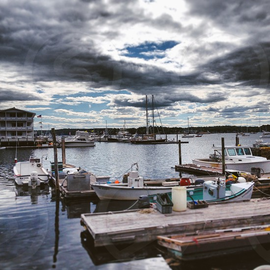 boats on body of water under gray and white sunny cloudy sky photo