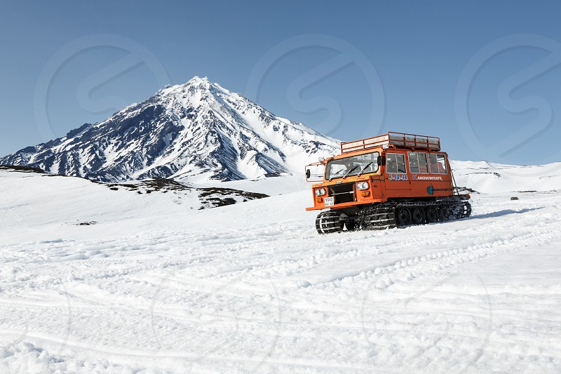 AVACHA PASS KAMCHATKA PENINSULA RUSSIAN FEDERATION - APRIL 26 2014: Snowcat transportation sportsman (skiers and snowboarders) on snowy slopes of mountains on background of cone of Koryak Volcano. photo