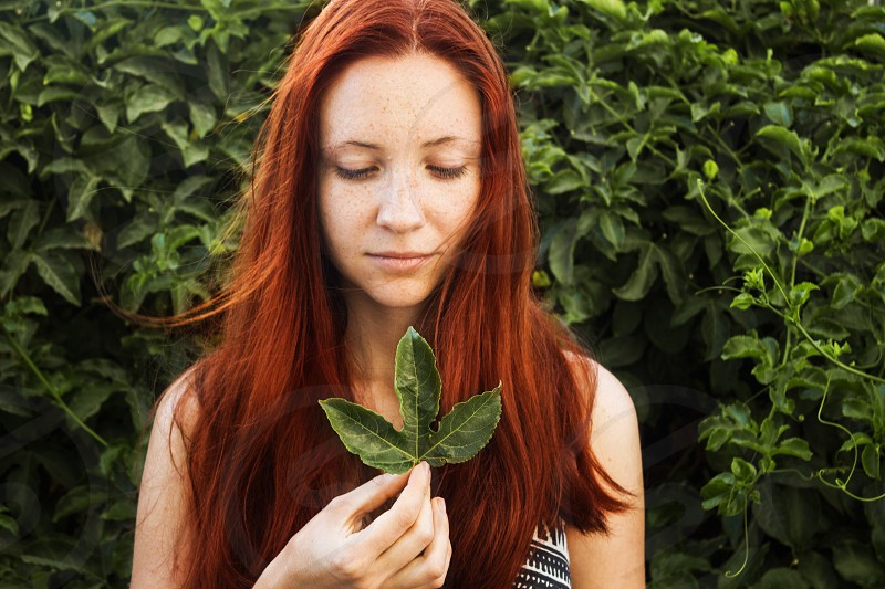 woman with orange hair holding a green leaf with right hand at daytime photo