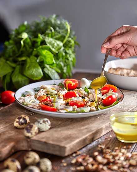 Female hand puts mustart sause to the plate of freshly cooked homemade salad from natural ingredients on a wooden table. photo
