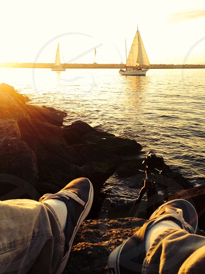 shoes and rocks by water facing sailboats photo