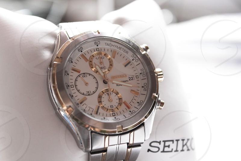 silver link bracelet white round chronograph seiko watch reading 11:18 photo