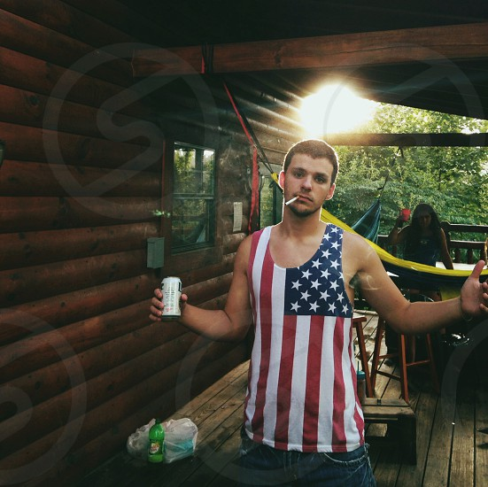 man in us flag inspired tank top open his arms wide open photo