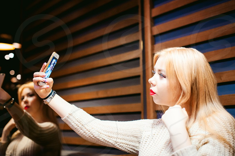 young blond woman in a knitted sweater making a selfie photo on a smartphone sitting at a table in a cafe spending time alone doing internet communication photo