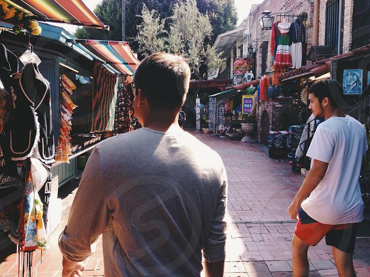 man in grey long sleeved shirt walking near man in white t-shirt photo