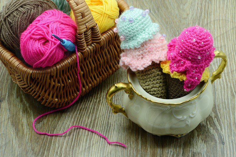 crochet ice cream cone in a sugar box with wool on table background. Basket with wool balls aside. photo