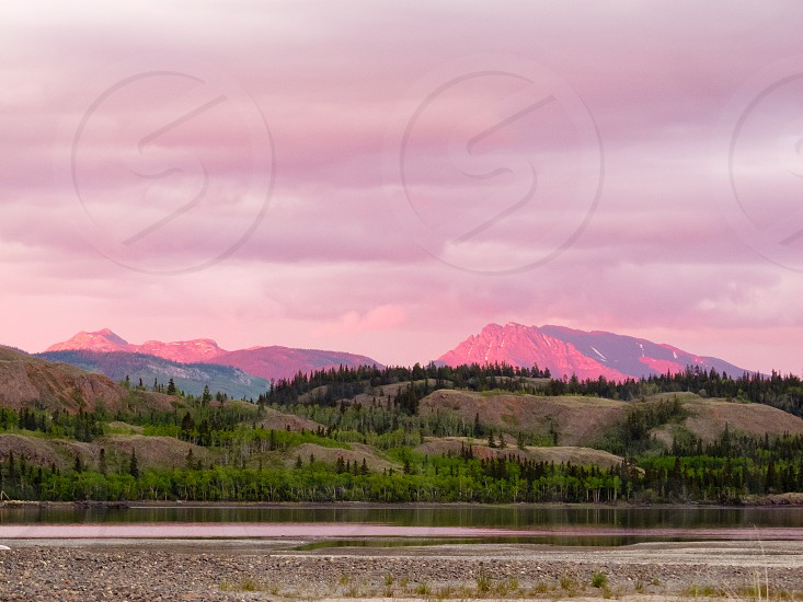 Distant mountains glowing in sunset light at Lake Laberge Yukon Territory Canada photo