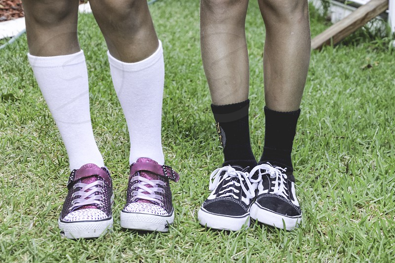 young love friendship side by side low section of young people in sneakers and socks standing together on the grass  photo