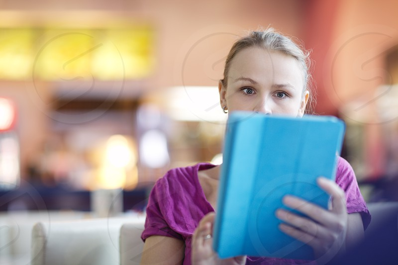 Woman in a terminal or waiting room using her tablet computer to surf the internet close up of her holding it up in front of her face she is very surprised and shocked with something photo
