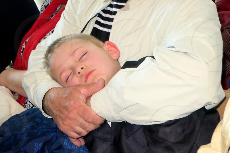 boy in black dress shirt sleeping on man's tummy photo