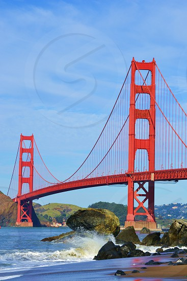 Golden Gate Bridge and blue sky with waves crashing on rocks photo