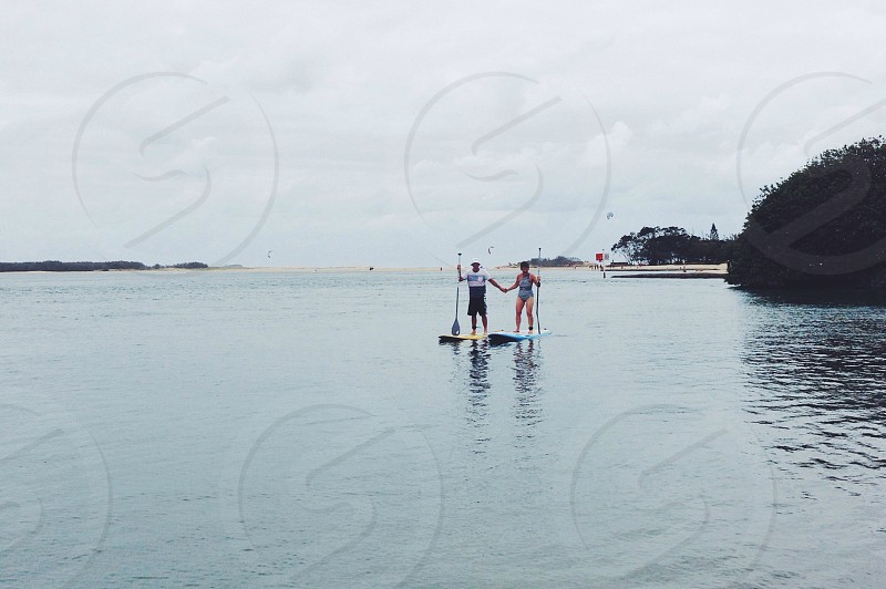 two people standing on surfboard holding paddle photo