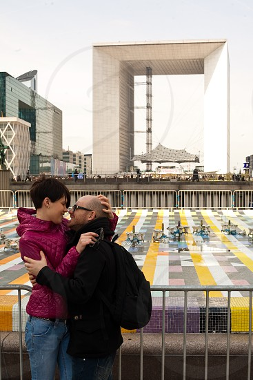 woman and man hugging on the metal fence background by concrete structures during daytime photo