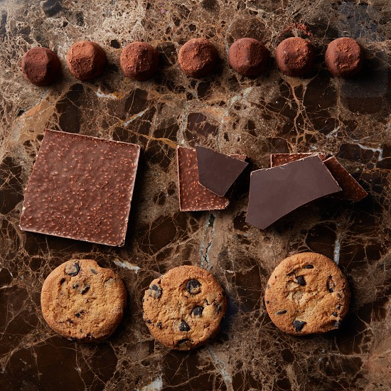 chocolate pieces truffle candy and cookies on a marble dark background photo