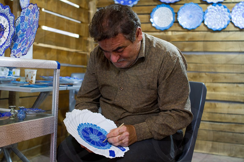 Persian artist doing Mina-Kari painting on plates traditional Persian handmade art Mina art painting portrait people doing art photo