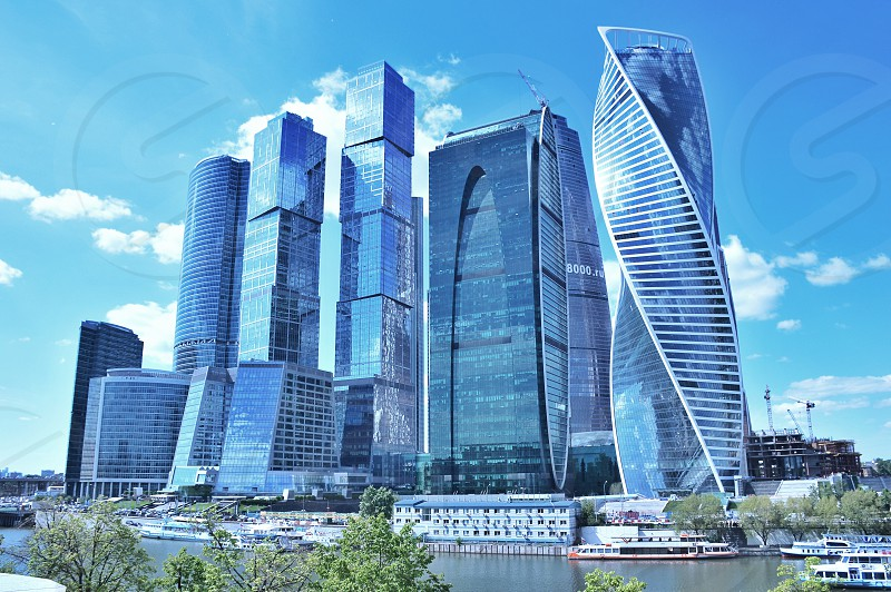 city buildings beside body of water under blue sunny cloudy sky photo