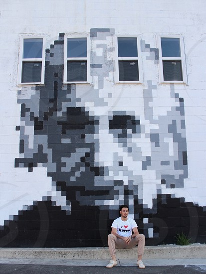 man in white and black i heart korea printed crew neck shirt sitting in front of alber einstein pixilated illustration photo