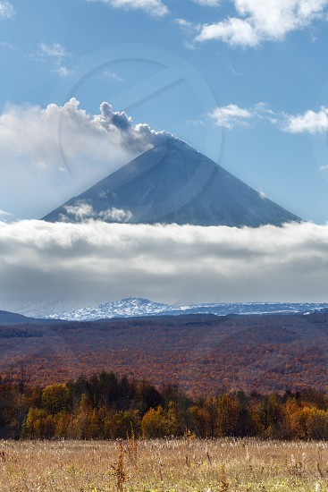 Volcanic landscape of Kamchatka: explosive-effusive eruption of Klyuchevskoy Volcano: powerful plume of gas steam ash from crater volcano. Picturesque autumn view of volcanic eruption on sunny day. photo