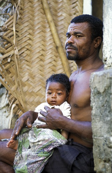 a men with his child in the city of Moutsamudu on the Island of Anjouan on the Comoros Ilands in the Indian Ocean in Africa.    photo