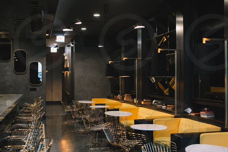 restaurant white black yellow sofa white table and stainless steel chairs recessed lamps and wall mirror photo