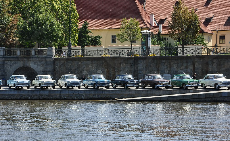 row of classic cars parked beside waterway photo