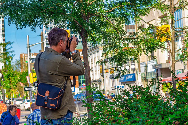A man standing in a market square positions his camera setting up a shot. photo