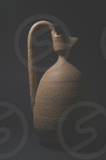 beige stone pitcher in the dark photo